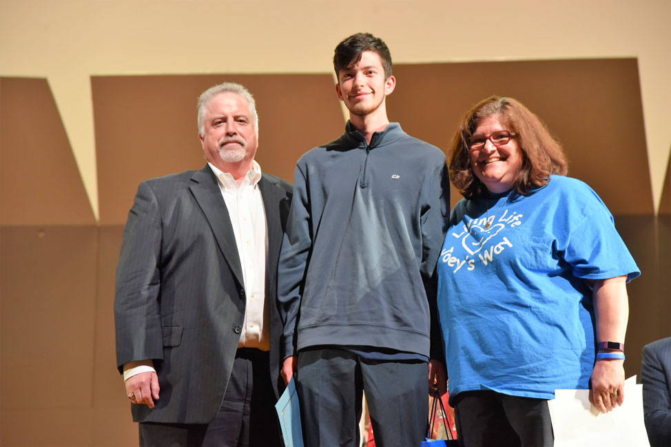 Huntington Class of 2019 member Daniel Thompson with Glen and Anne Manaker at the award ceremony